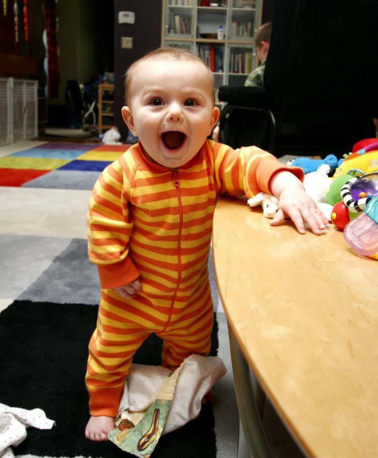 baby walking along furniture
