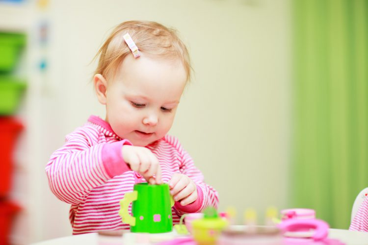 Adorable little girl playing with toys in her room