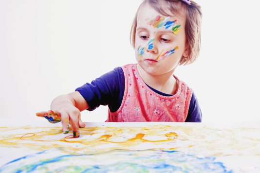 Little cute child girl painting on a white wall background (Creativity, education, child development in art, happy childhood, abilities concept)